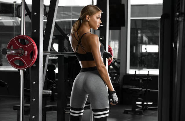 Athletic girl working out in gym. Fitness woman doing exercise.