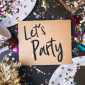Let's party brush stroke handwriting on golden greeting card with party cup,party blower,tinsel,confetti.Holiday celebrate party time.top view tabletop